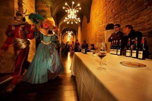 Participantes disfrazados en Carnaval del Vino Haro junto a la exhibición de vinos