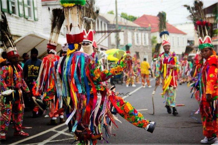 La gente celebra en la calle con trajes coloridos durante el carnaval de St Kitts