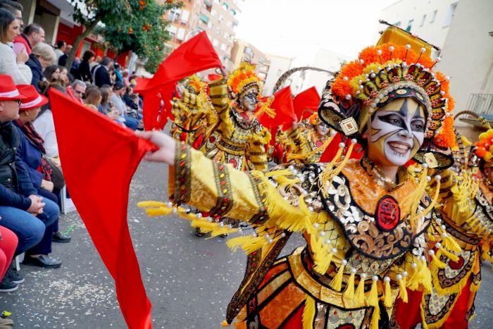 Las comparsas visten de prendas coloridas durante el desfile de carnaval de Badajoz que comienza al medio día