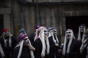 Las lamias visten ropas negras, pelucas blancas y llevan sus caras pintadas en el carnaval de Mundaca