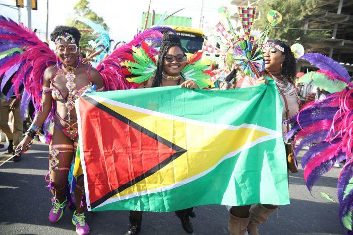 Las personas salen a las calles a festejar el carnaval de Guyana con prendas coloridas