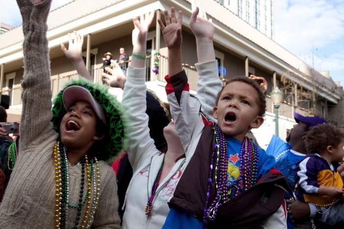 Las personas atajan los objetos que arrojan desde las carrozas en el Mardi Gras de Mobile