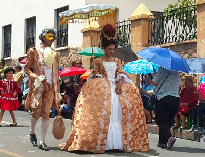 Las personas desfilan las calles visitiendo ropa de epoca durane los carnavales de sucre en Bolivia