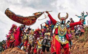 Las personas visten de trajes coloridos y máscaras en el entierro del diablo para los carnavales de Tilcara