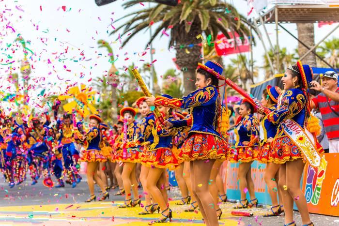 Los grupos de baile arrojan confeti a los participantes durante las competencias en el carnaval de Arica